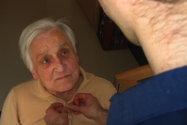 Senior Being Dressed By Caregiver