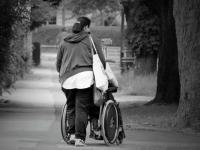 Woman walking away from camera while pushing wheelchair