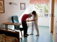 Nurse Woman Helping Senior With Walker