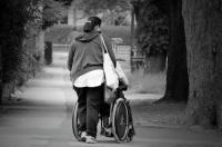 Woman walking away from camera while pushing wheelchair
