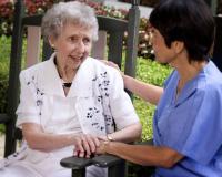 Female nurse sitting with elderly woman outdoors